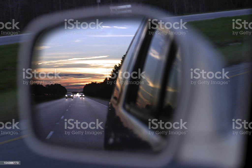 Sunset on a highway in the rear view mirror royalty-free stock photo