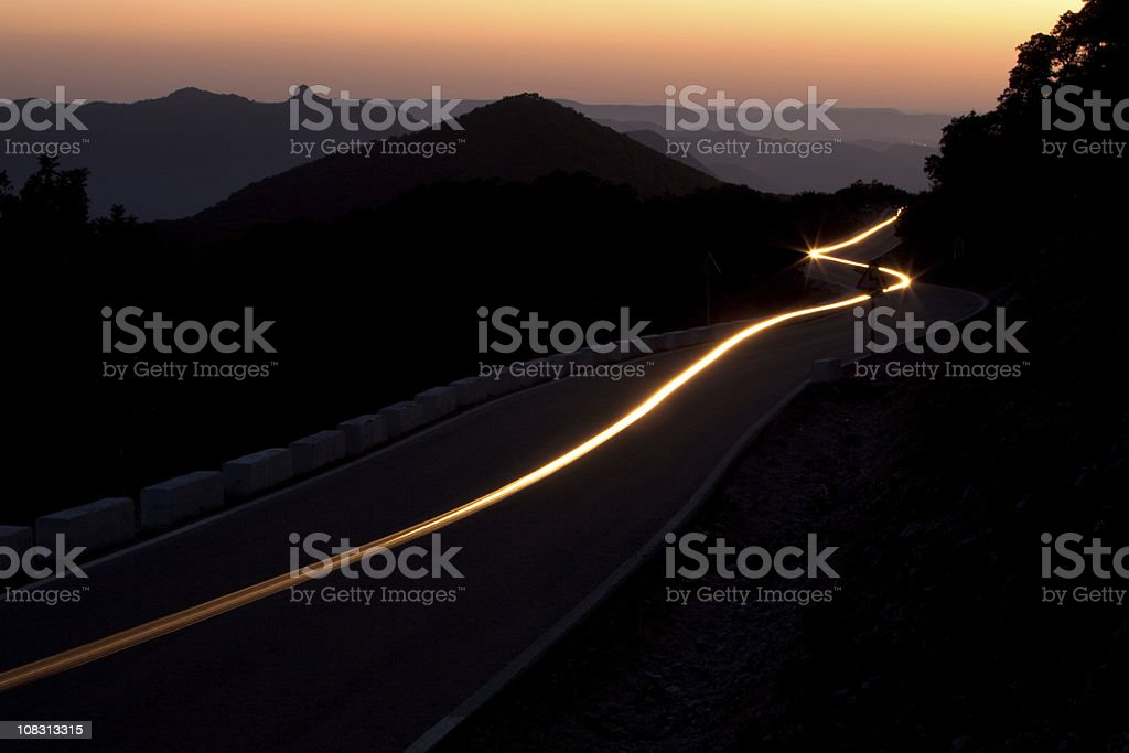 Sunset on a winding highway through the mountains stock photo