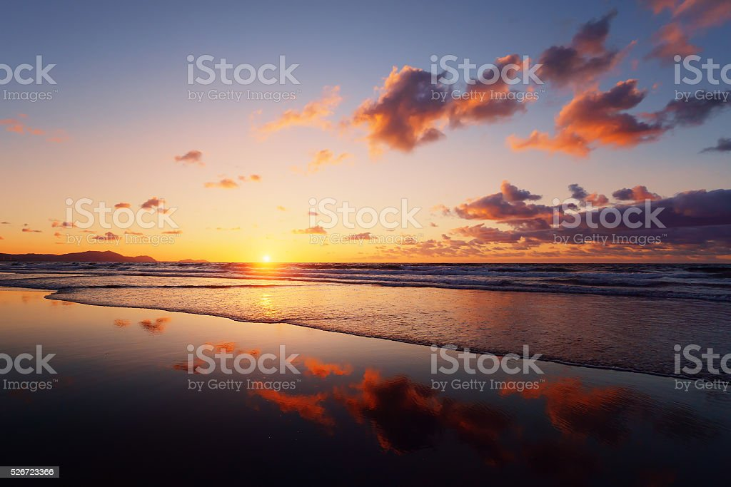 sunset on beach with cloud reflections stock photo