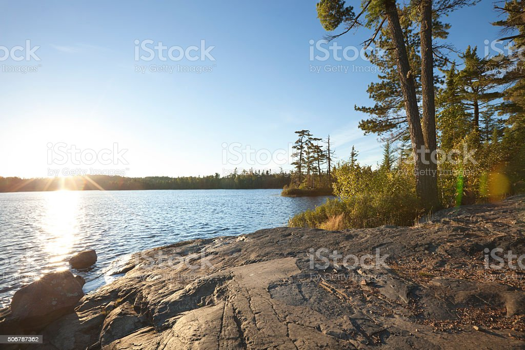 Sunset on lake with rocky shore in northern Minnesota stock photo