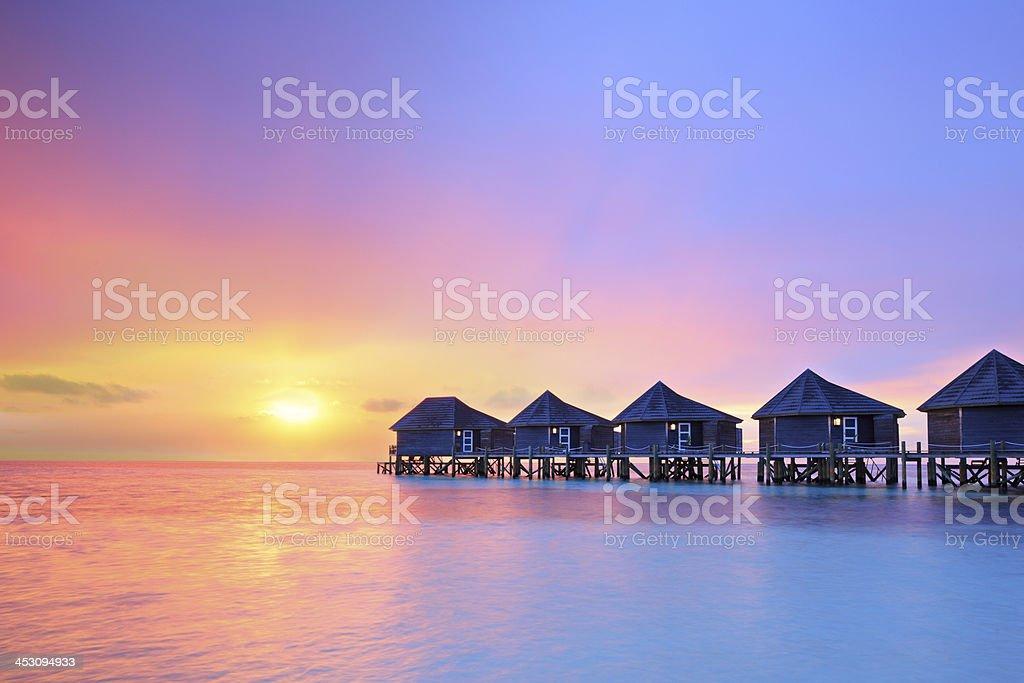 Sunset on Maldives island, water villas resort stock photo