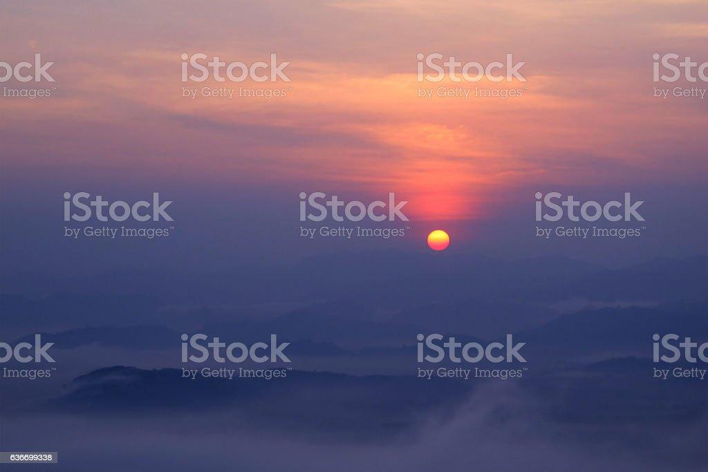 sunset on mountain with mist stock photo