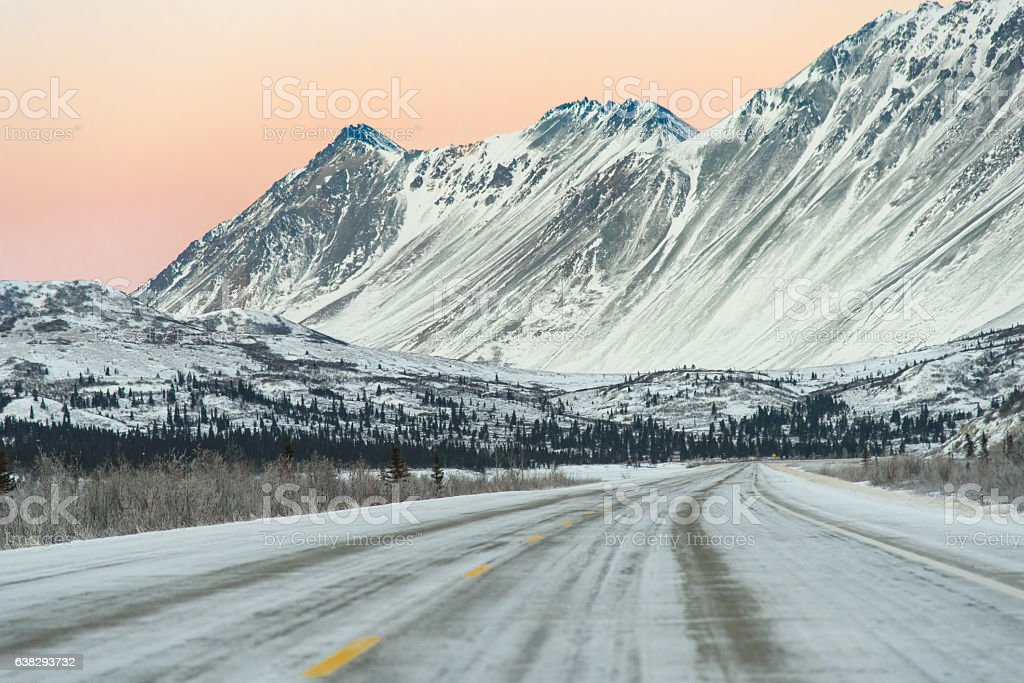 Sunset on Remote Alaska Highway With Snow Capped Mountains stock photo