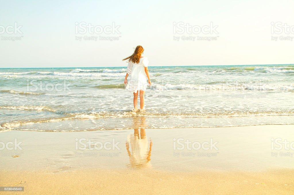 Sunset on the beach, beautiful woman enjoys stock photo