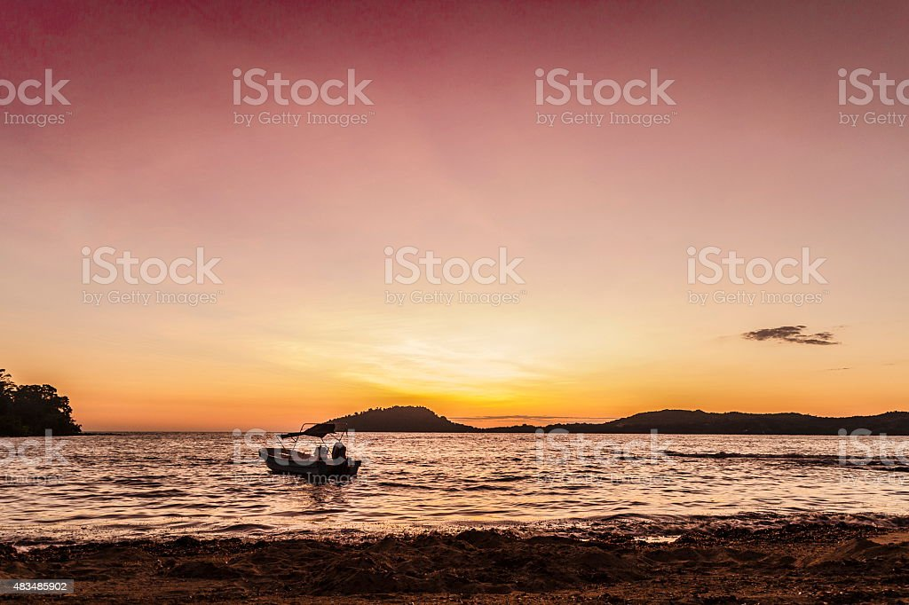 Sunset on the beach in Nosy Be Island with ship. stock photo