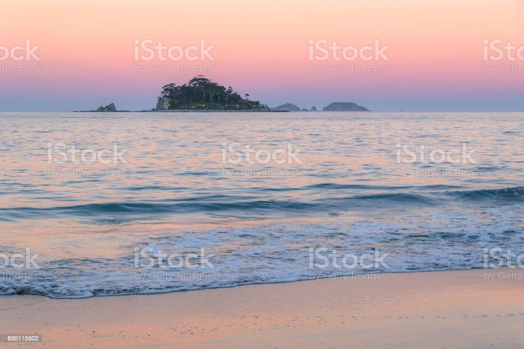 Sunset on the Coast with Island stock photo