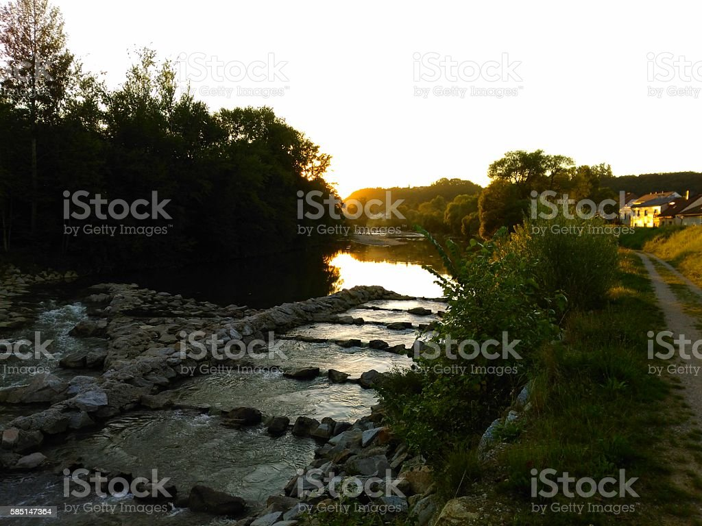 sunset on Austrian river with stone barrier stock photo