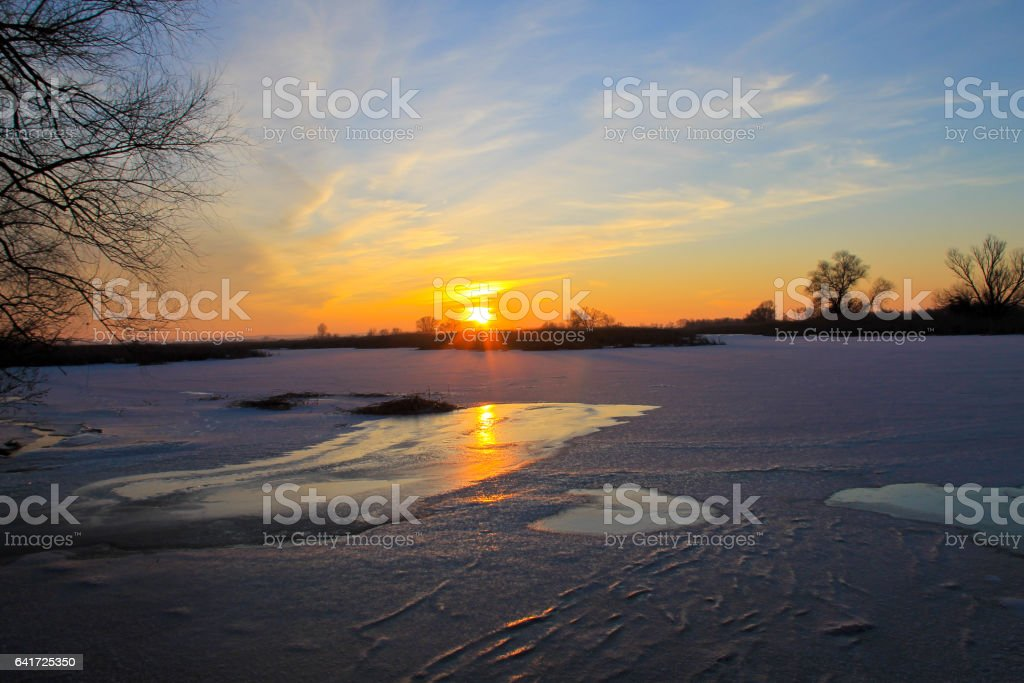Sunset over a frozen river Dnieper on winter stock photo