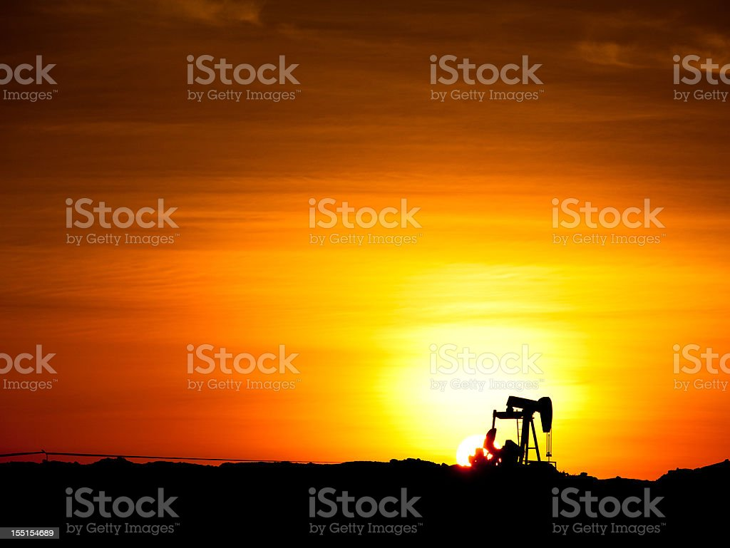 Sunset over an oil well stock photo