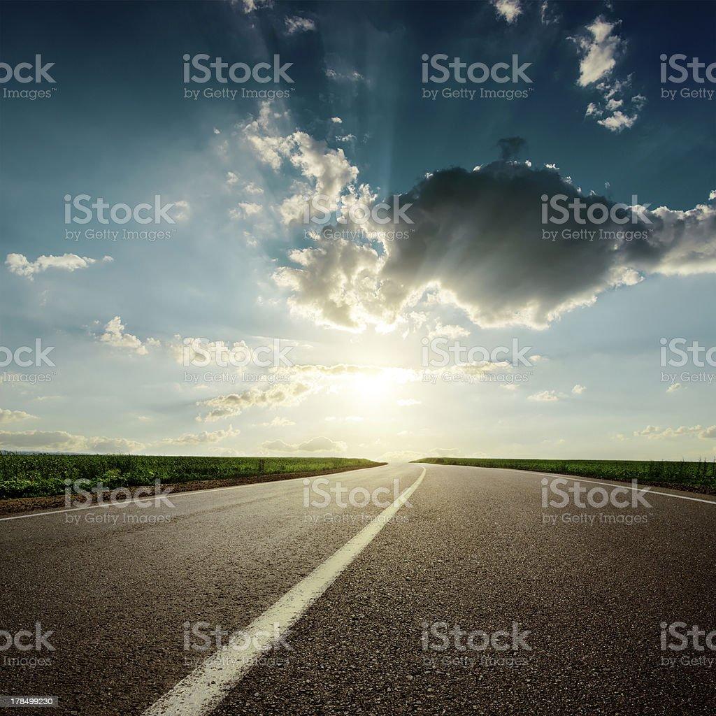 sunset over asphalt road royalty-free stock photo