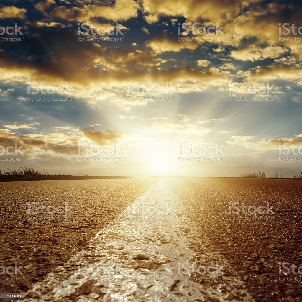 sunset over asphalt road with central white line stock photo