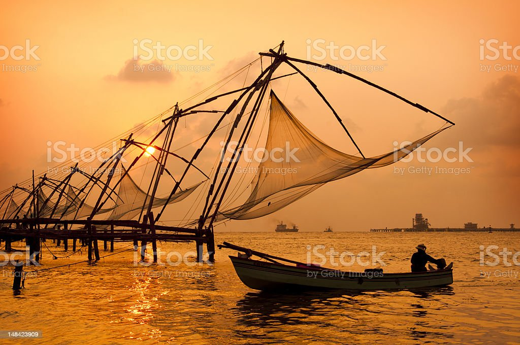 A sunset over Chinese fishing nets by a canoe in Cochin stock photo