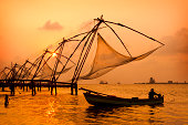 A sunset over Chinese fishing nets by a canoe in Cochin
