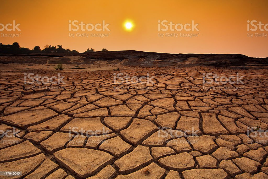 Sunset over cracked land and arid terrain royalty-free stock photo