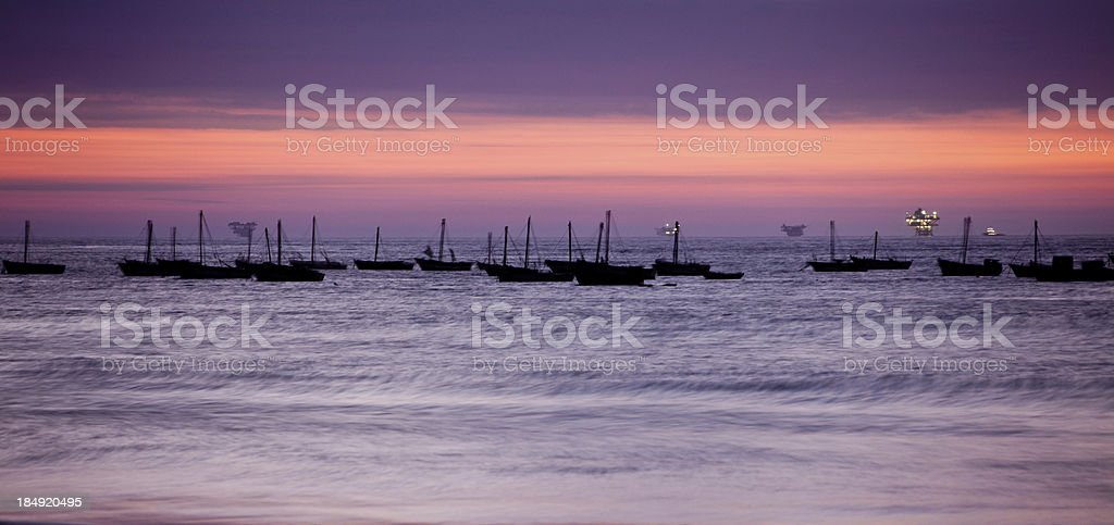 Sunset over fishing boats in rural Peru with oil platforms stock photo