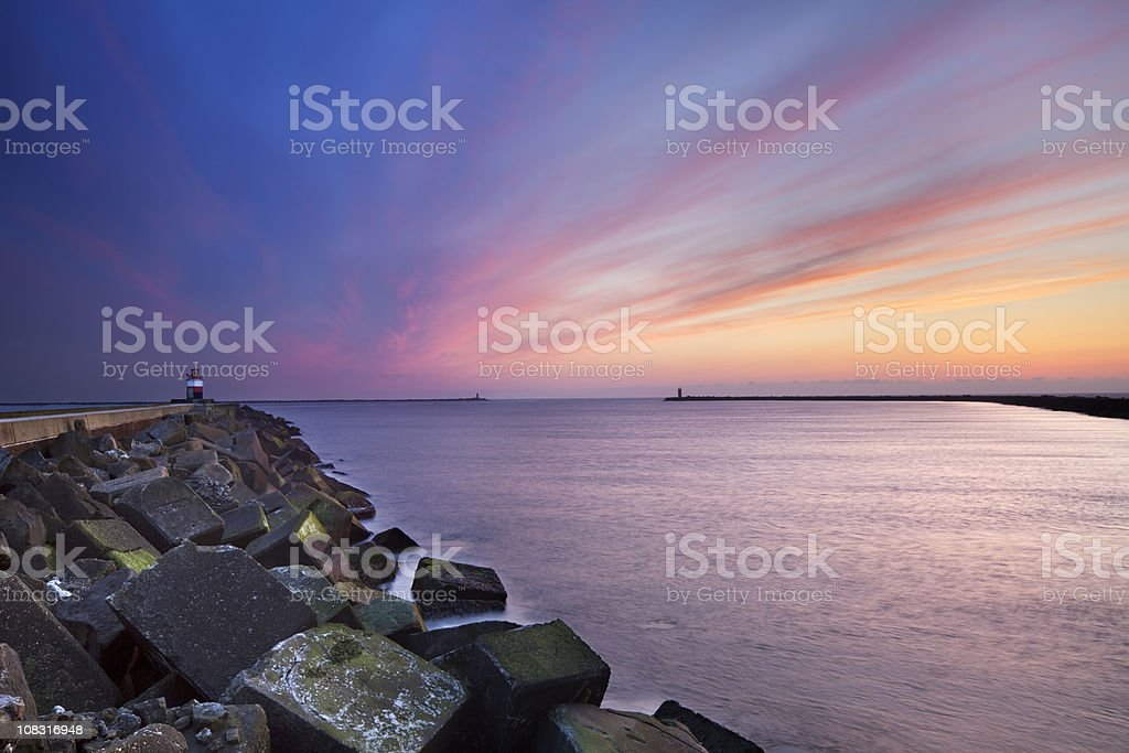 Sunset over harbour entrance at sea in IJmuiden, The Netherlands stock photo