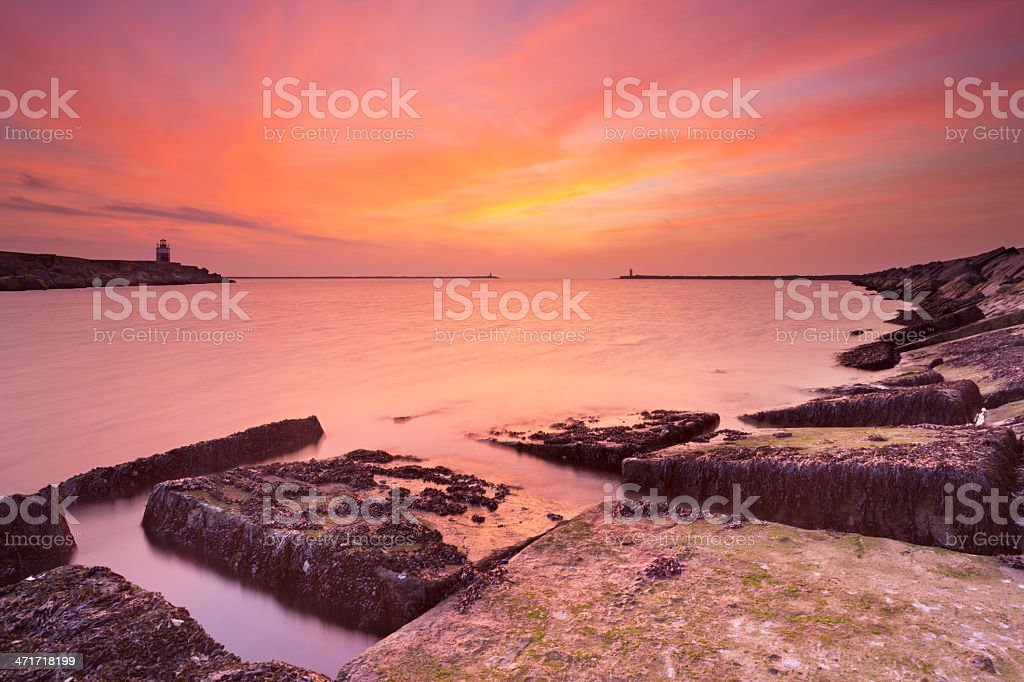 Sunset over harbour entrance at sea in IJmuiden, The Netherlands royalty-free stock photo