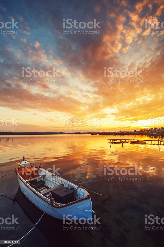 Sunset over lake and a boat with sky water reflecting stock photo