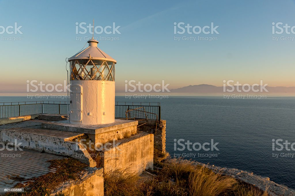 Sunset over Lighthouse in Kavala and Thassos island in background stock photo