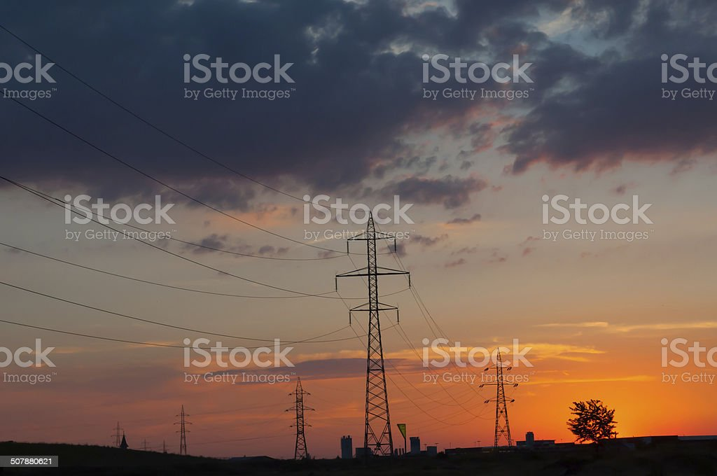 sunset over power poles, blocks of flats and a tree royalty-free stock photo