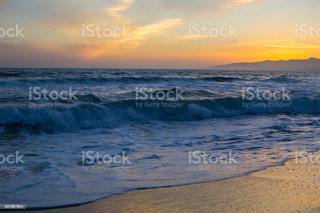 Sunset over rolling waves stock photo