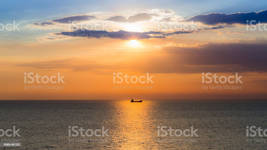 Sunset over seacoast with small fishing boat stock photo