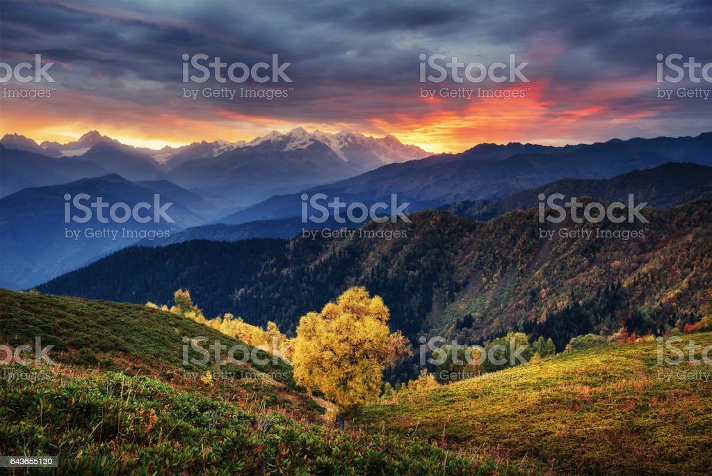 Sunset over snow-capped mountain peaks. The view from the mounta stock photo