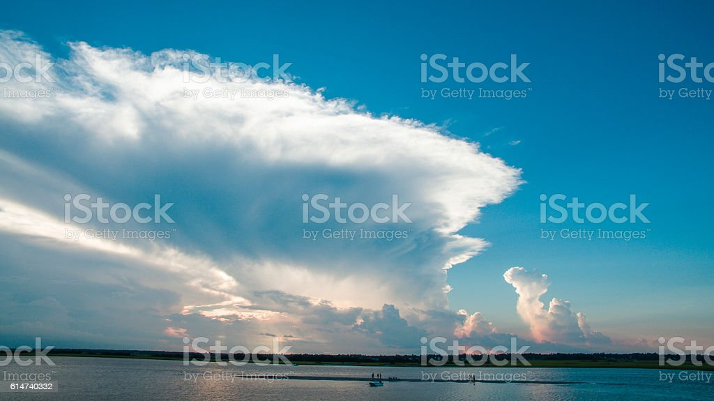 Sunset over the inlet with people on a sandbar stock photo