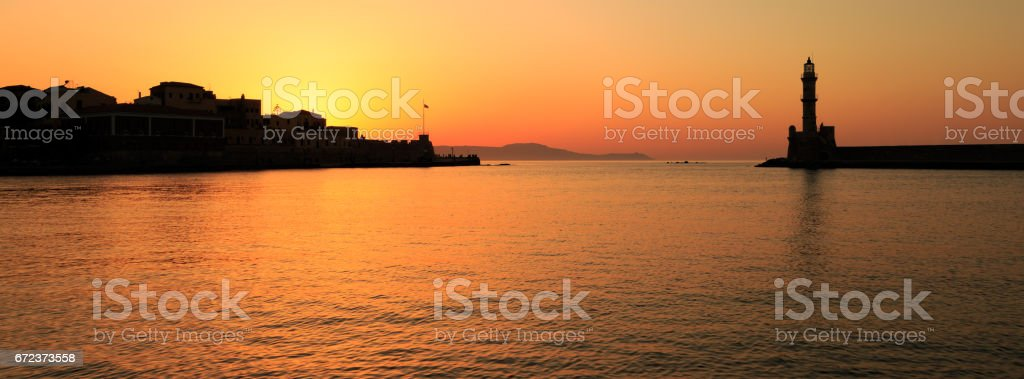 Sunset over the lighthouse and old Venetian harbour in Chania, Crete stock photo