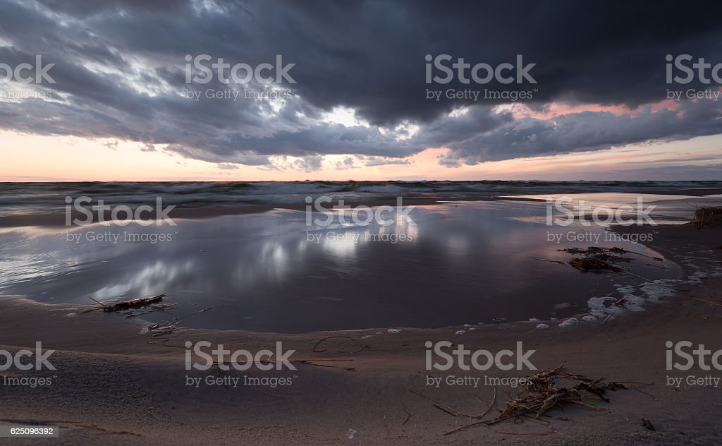 Sunset over the ocean with the clouds reflecting in the water stock photo