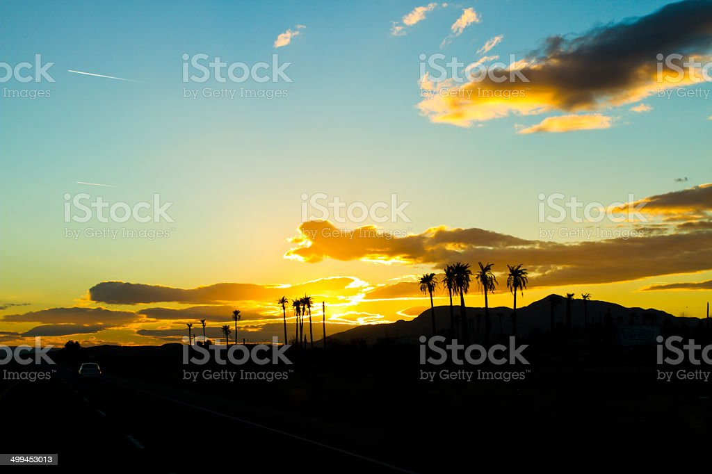 Sunset over the ocen near a beach with palm trees royalty-free stock photo