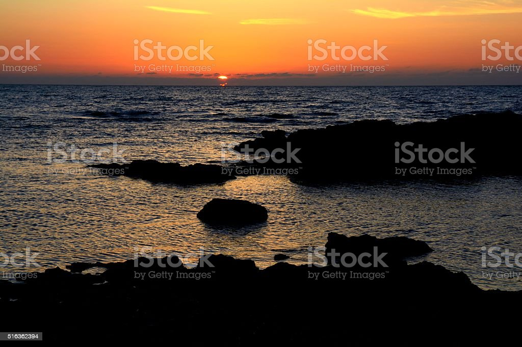 Sunset over the sea with silhouette stock photo