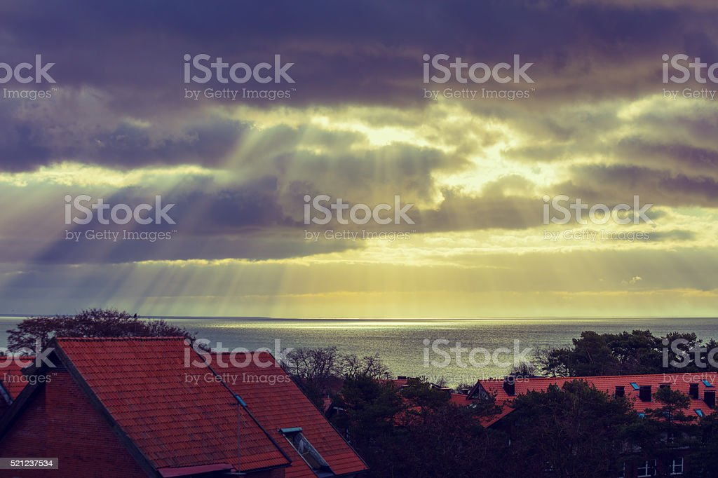 Sunset over the village, located on the sea shore stock photo
