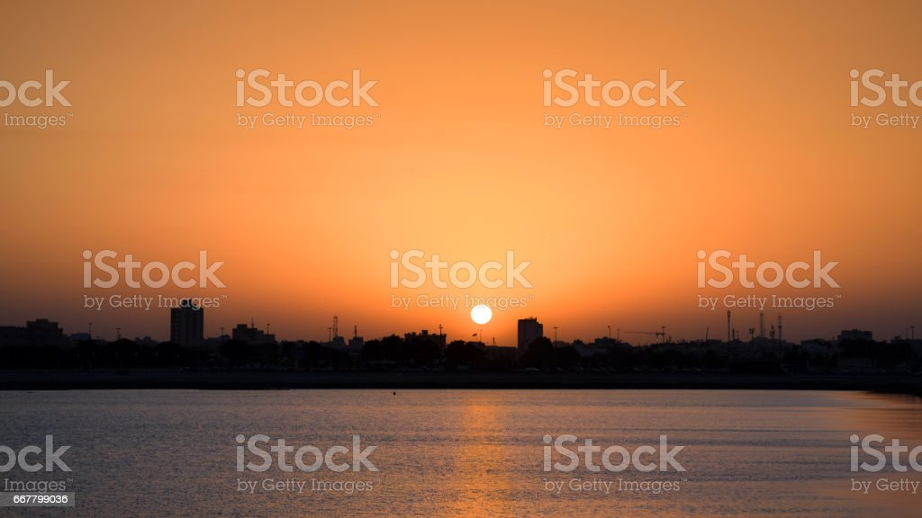 Sunset over water and city silhouette stock photo