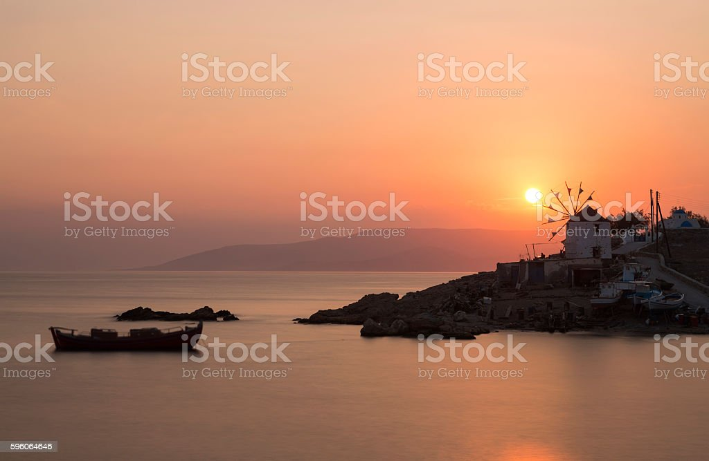 Sunset over windmill in Cyclades island of Greece stock photo