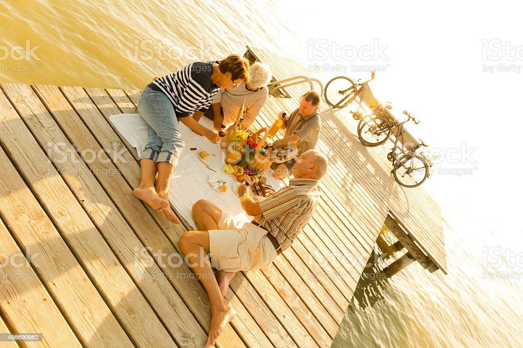 sunset picnic on pier stock photo