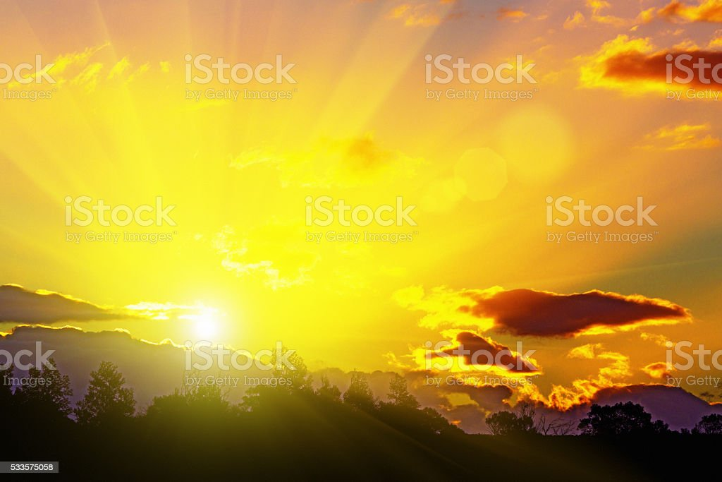 Sunset rays, gold-rimmed clouds: golden end to a perfect day; stock photo