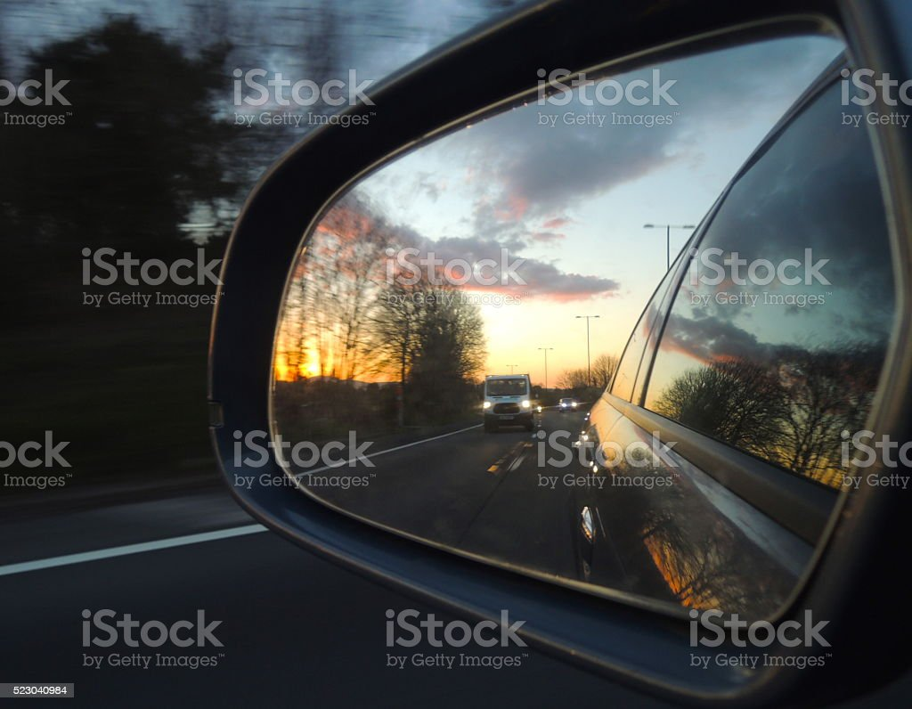 sunset reflected in car wing mirror stock photo