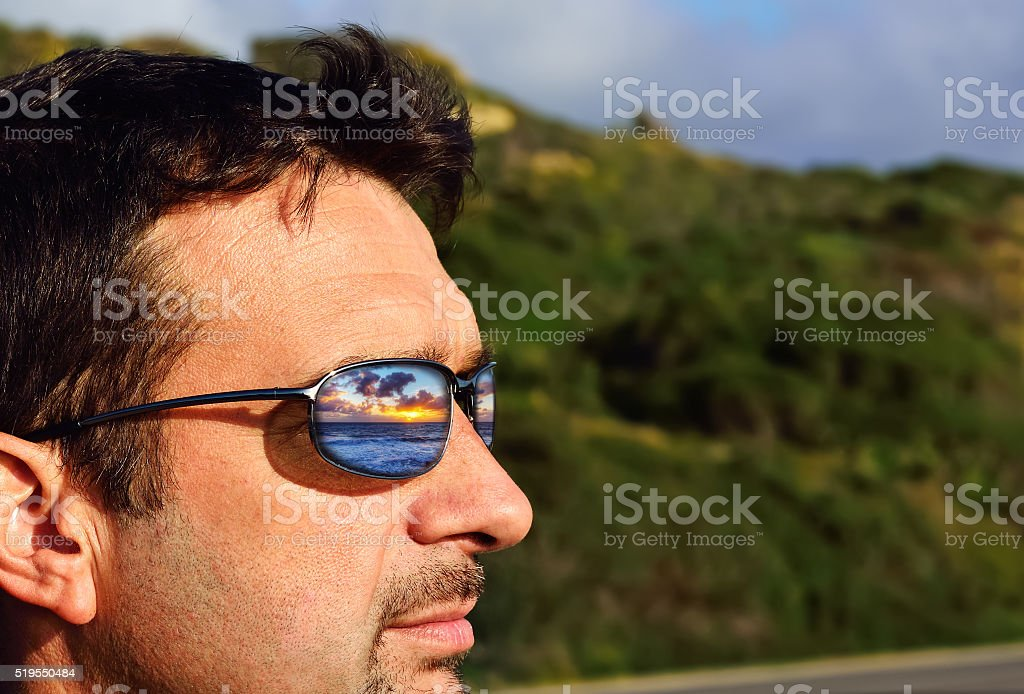 sunset reflected in sunglasses lens stock photo