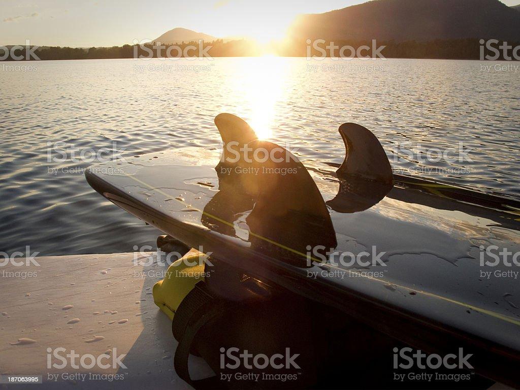 Sunset reflecting off surfboard. stock photo