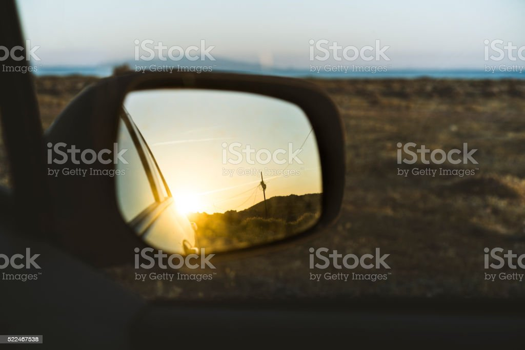 Sunset reflection on the wing mirror of car stock photo