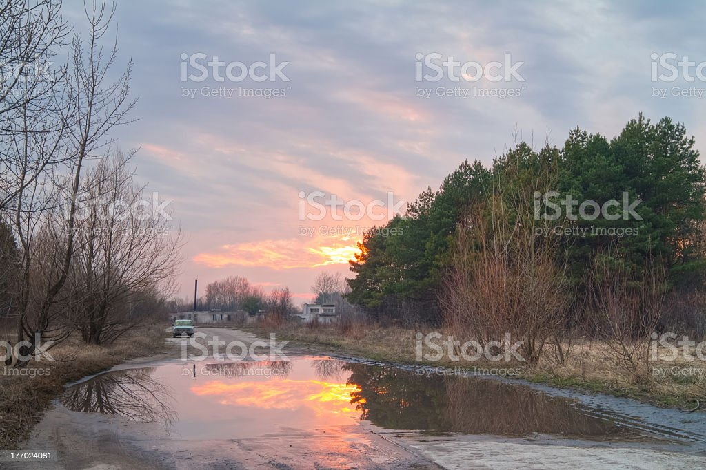 Sunset reflects in a puddle. royalty-free stock photo
