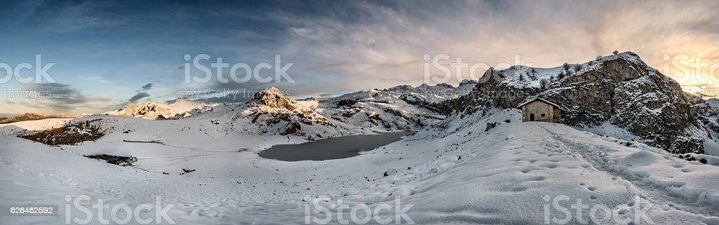 Sunset Refuge house, lake and mountains in snowy Asturias winter stock photo