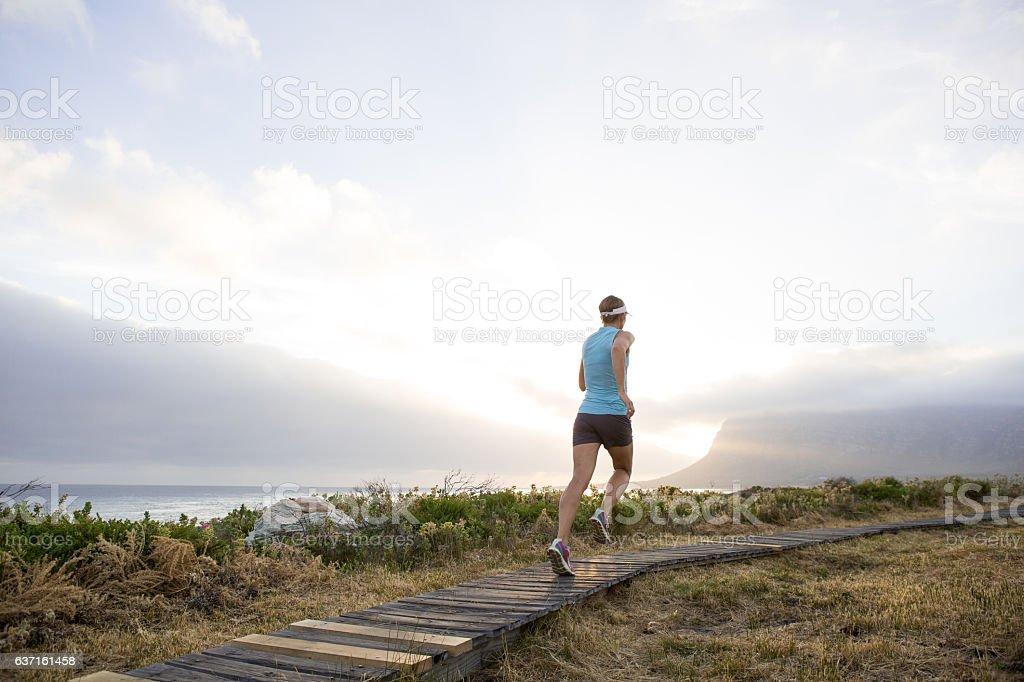 Sunset run along a coastal path stock photo