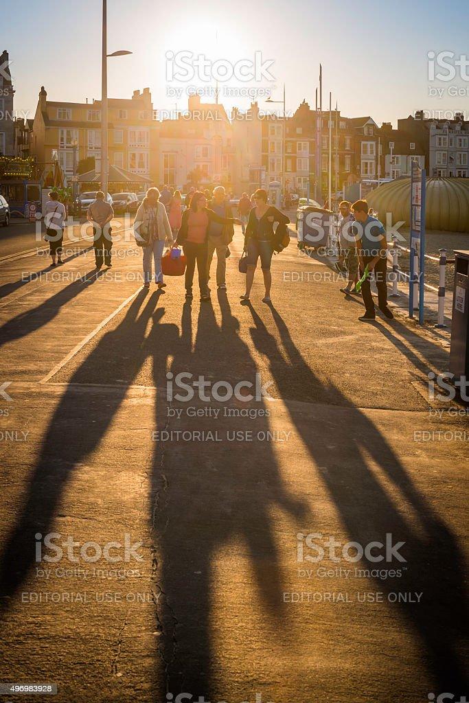 Sunset shadows of seaside tourists on beach promenade Weymouth UK stock photo