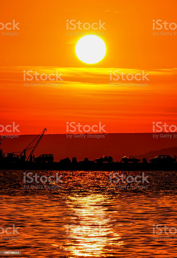 Sunset, shore, sea and cars stock photo