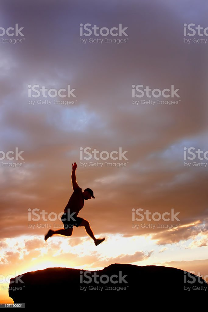 sunset silhouette man jumping royalty-free stock photo