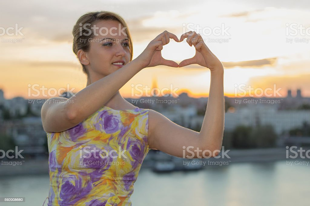 Sunset sky with woman hands making heart shape stock photo