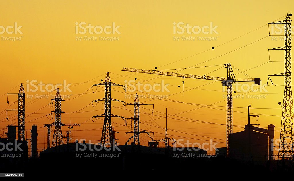 Sunset skyline of power lines and construction crane stock photo