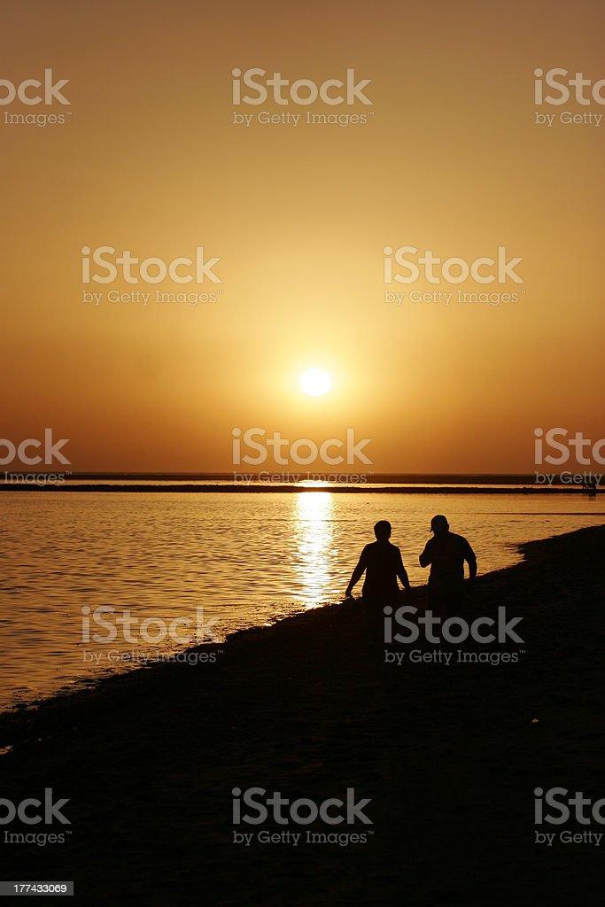 sunset stroll on beach royalty-free stock photo